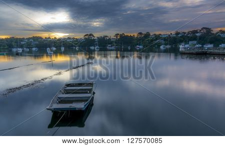 Dawn on the river Fal in Cornwall, England - long exposure, with a boat moored in the forefront of the frame