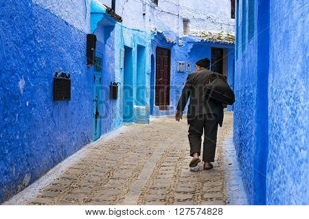 Chefchaouen Morocco - April 10 2016: An old man walking in a street of the town of Chefchaouen in Morocco.