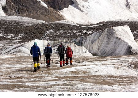 Group of Mountain Climbers with High Altitude Boots and Clothing Crossing Ice Section During Ascent of Alpine Expedition in Asia Mountain Area