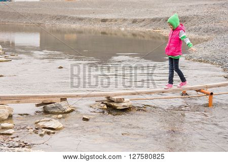 Little Girl Cautiously Goes On The Board Across The Pond