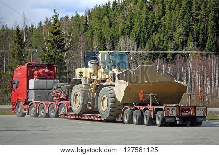 FORSSA, FINLAND - APRIL 23, 2016: Scania 164G semi truck transports a heavy duty Volvo L350F wheel loader as oversize load on lowboy trailer rear view.