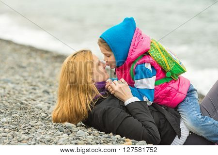 Five-year Girl Sitting Astride A Mother Who Is Lying On The Pebbly Shore Of The Sea, And Kisses Her