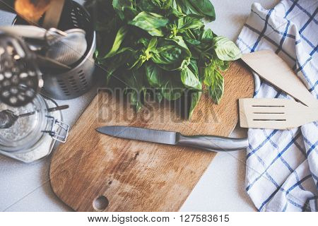 A bunch of basil on the board on the kitchen table, home cooking utensils for cooking, top view