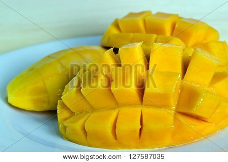 Beautiful nicely cut yellow mango on the dish