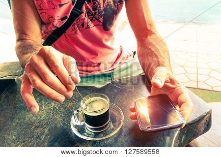 Man stirring coffee and holding smart phone at beach bar cafe restaurant - Hands with coffe cup and mobile top view on wooden table - Concept of relaxation humane habits and new technology addiction