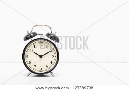 Retro style alarm clock on a simple background with ample copy space.