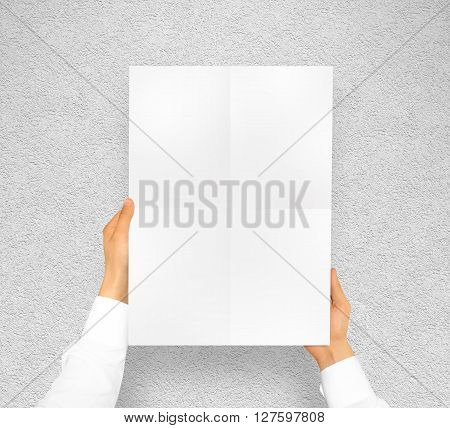 Hand holding poster mock up. Nice mockup to show your design, picture or illustration. Blank sheet in hands near the textured wall. Display movie theatre cinema film with poster holder. Leaf design.