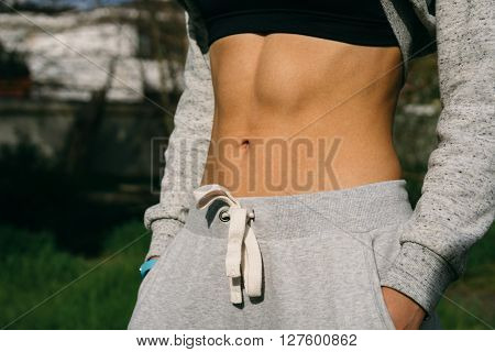 Belly Athletic Girl Who Is Dressed In Pants And A Sports Bra