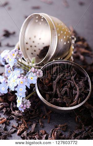 Strainer Full Of Dry Tea Leaves With Blue Flower