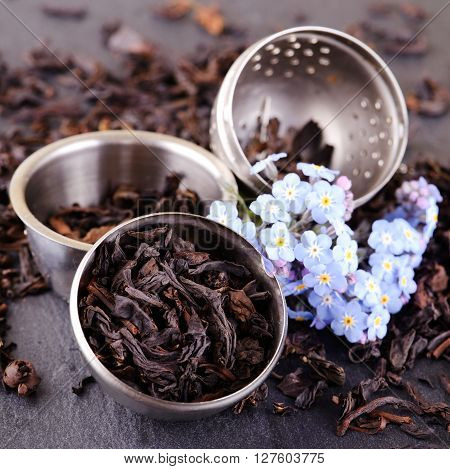 Strainer Full Of Tea Leaves And Blue Flower On Slate