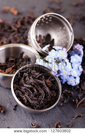 Tea Strainer On Black Slate Stone With Blue Flower