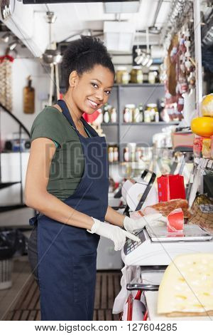 Happy Saleswoman Weighting Cheese On Weight Scale