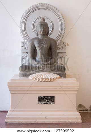 Thanjavur India - October 14 2013: Cholas era statue of Buddha at the Thanjavur Palace. Hard granite placed against white wall.