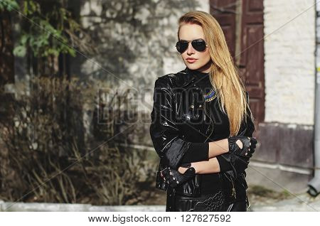 portrait biker sexy woman blonde in sunglasses and black jacket