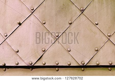 Industrial textured background. Texture metal surface of aged metal plates with small rivets on them.