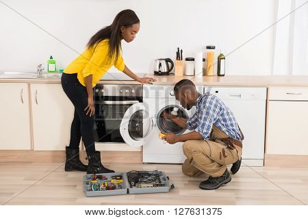 Technician Repairing Washing Machine