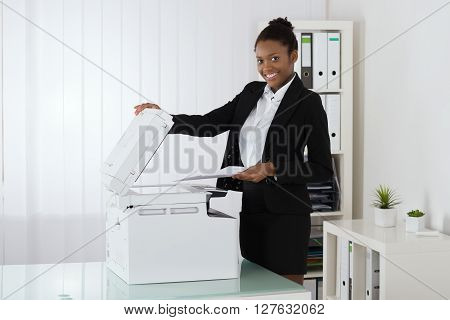 Smiling Businesswoman Using Photocopy Machine