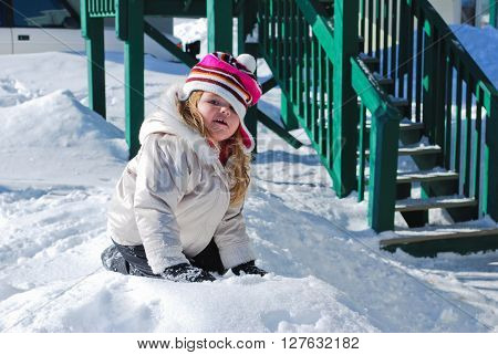 Adorable little girl in toboggan playing in the snow next to set of stairs.