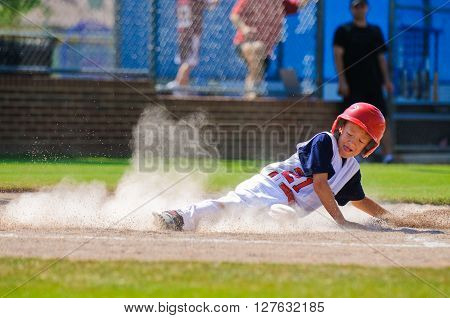 Youth baseball player sliding in at home plate. poster