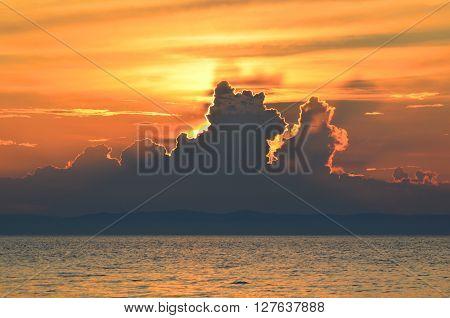 Beautiful maroon sunset on lake Baikal. A hot summer day.