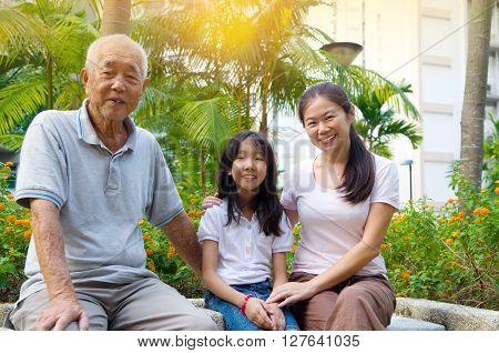 Portrait Of three Generation Chinese Family Relaxing at outdoor Park