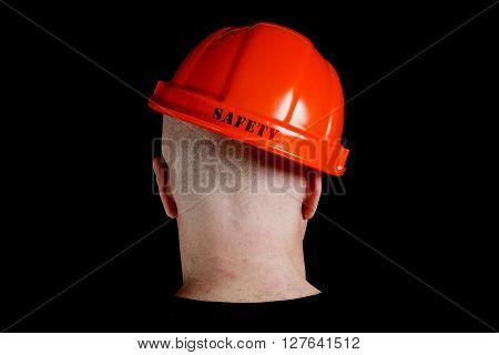 Construction worker in hard hat with an inscription safety on gray background