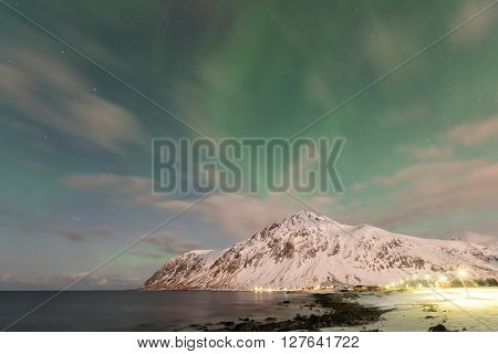 Northern lights over the sea at Vareid Lofoten Islands Norway in the winter. poster