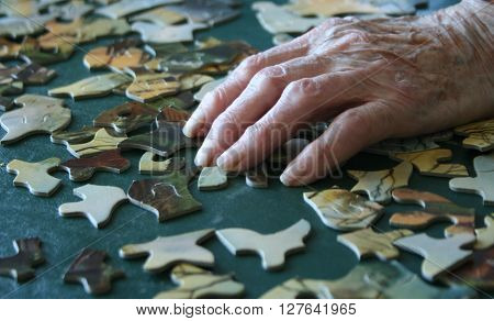 Elderly woman's arthritic fingers and  hand building puzzle