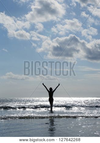 Woman silhouette with hands up on the beach
