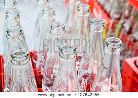 BANGKOK, THAILAND - JULY 28: Empty recycle bottles of Coca Cola in red plastic box on July 28, 2015 in Bangkok, Thailand. Coca Cola drinks are produced and manufactured by The Coca-Cola Company