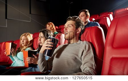 cinema, entertainment and people concept - friends with popcorn and soda watching horror or thriller movie in theater