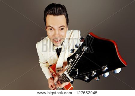 Imposing male musician  plays and sing in the style of the sixties. Rock'n'roll, jazz man. Beat generation.