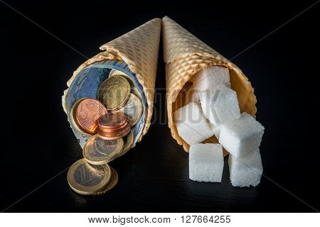 Wafer cones with sugar cubes in one and money (euro notes and euro cents coins) symbolising sugar tax in EU