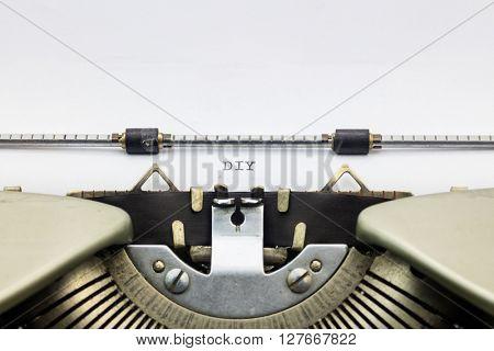 Close-up of abbreviation DIY on typewriter sheet