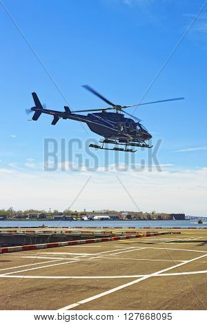 New York, USA - April 25, 2015: Black Helicopter landing on helipad in Lower Manhattan New York USA on East River. Pier 6. East River and skyscrapers on the background