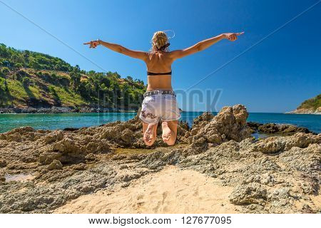 Happy woman with bikini and shorts, jumping in the air on Ya Nui Beach, a little cove divided by a rocky cape, Phuket, Thailand, Asia.