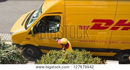 PARIS FRANCE - APR 21 2016: Courier enters DHL yellow delivery van after delivering the on time delivering package parcel