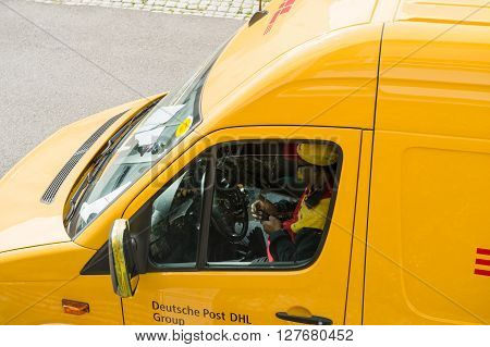 PARIS FRANCE - APR 21 2016: Courier inside DHL yellow delivery van after delivering the on time delivering package parcel enters the data into mobile terminal