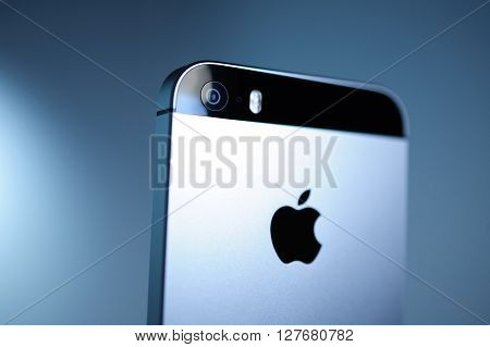 PARIS FRANCE - APR 21 2016: Rear view of the new Apple iPhone SE on blue background with Apple logo and detail of the new Camera - it features updated processor 4K rear camera touch id retina display