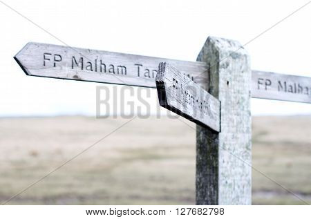 Under exposed Wooden sign post on moors at Malham Cove, Yorkshire, UK