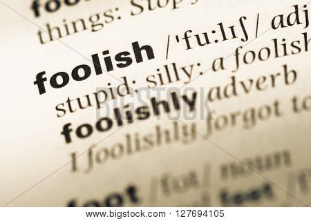 Close Up Of Old English Dictionary Page With Word Foolish.