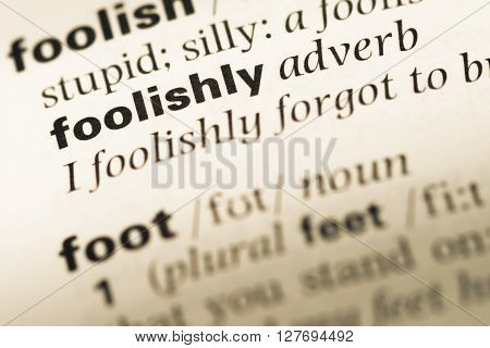 Close Up Of Old English Dictionary Page With Word Foolishly.