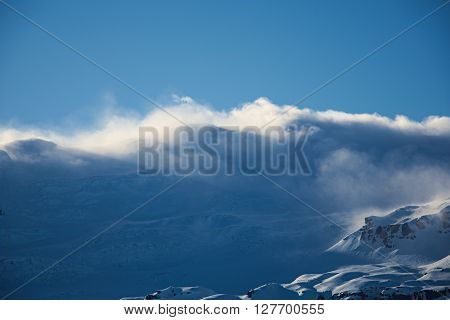 Snow-blown mountain chain at sunset and blue sky in Iceland