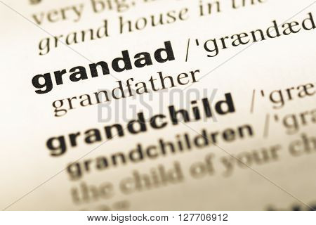 Close Up Of Old English Dictionary Page With Word Grandad.