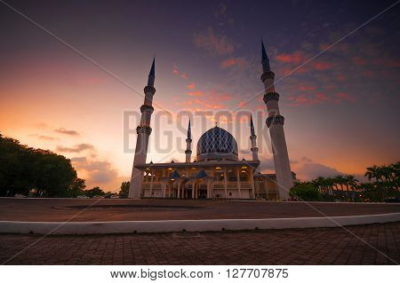 Dramatic Sunset With Vibrant Color Over Mosque (Sultan Salahuddin Abdul Aziz Shah).slightly motion blur and soft focusnoise due to long exposure photography.