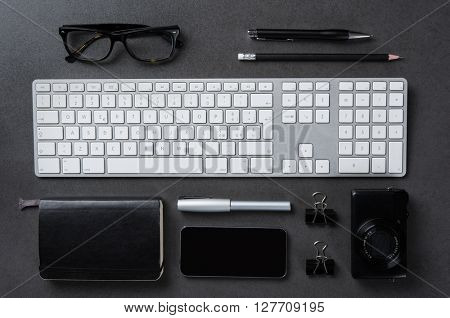 High angle view of a professional desktop. Top view of tidy desk in a business office. Close up of keyboard, organizer, camera, pen, smartphone, pencil and glasses on blackboard background.