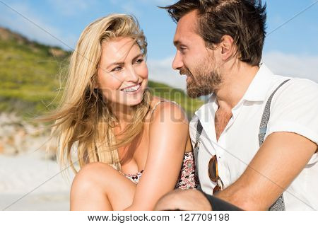 Cheerful young couple sitting on the beach looking at each other. Couple in love at the beach.Smiling woman looking her boyfriend in a summer day.