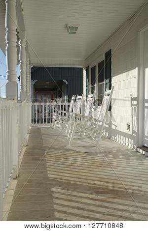 A row of four used and weathered white painted wooden country style rocking chairs on a worn porch at sunrise on a sunny day.