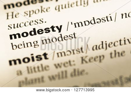 Close Up Of Old English Dictionary Page With Word Modesty.