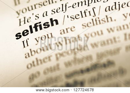 Close Up Of Old English Dictionary Page With Word Selfish.